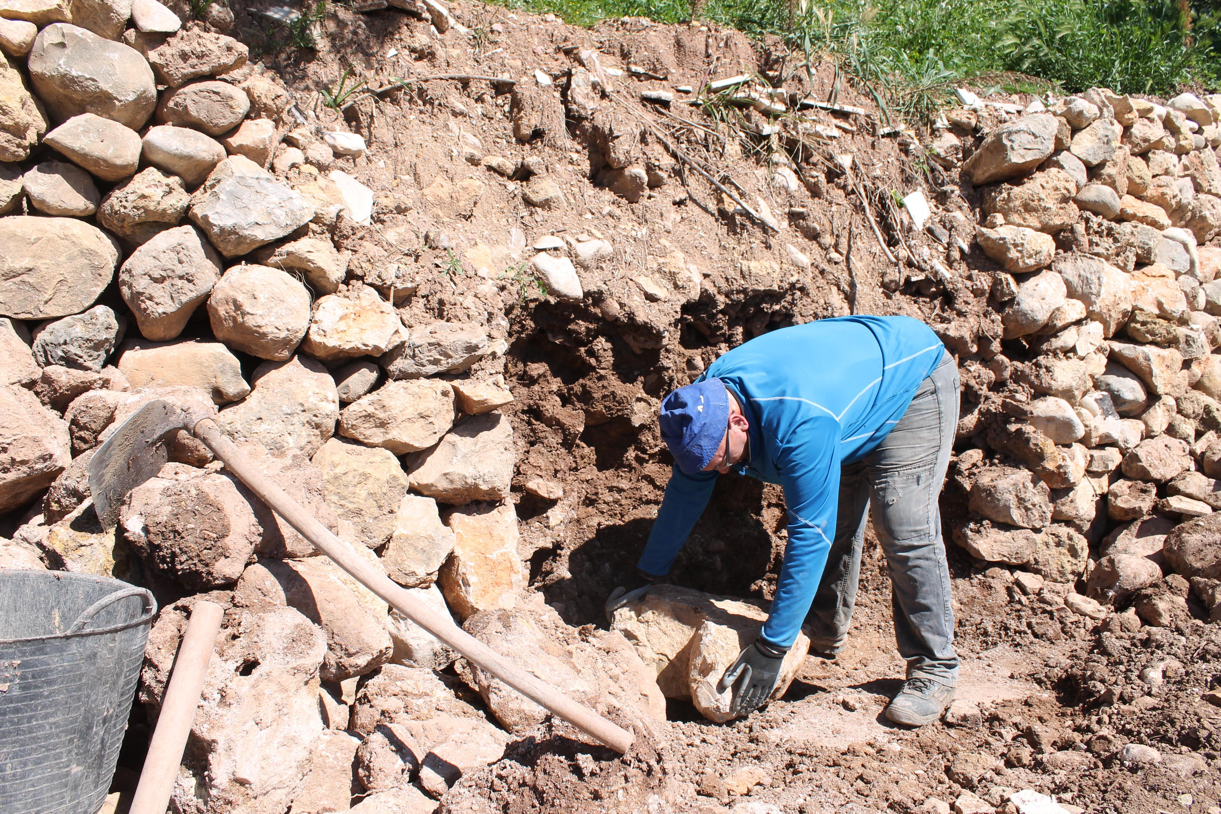 """Vecino de Alcalalí reparando un """"marge"""" con la técnica de construcción de la piedra en seco."""